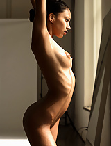 A perfect little ballerina admires herself in the mirror as she stretches her slender body.